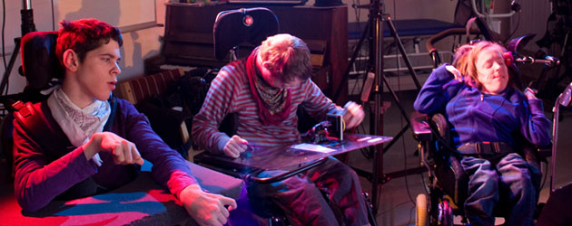 Three musicians in wheelchairs playing using switches